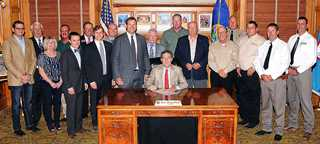 DU Kansas volunteer Doug Unruh (2nd from left) witnesses Governor signing outdoors proclamation