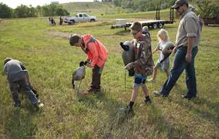 Kids help set up decoys during the duck gear demonstration.