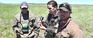 "Jim Olson, Luis Alvarez, and Adam McDaniel examine mallard eggs using a ""candling"" technique to determine incubation time."