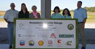 Partners pose with the Rockefeller Unit 4 sign during the dedication event.