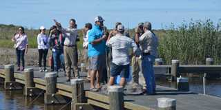 Dedication attendees met people crabbing and fishing on the recently completed Unit 4 water-control structure at Rockefeller.