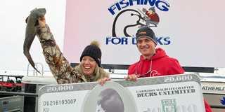 Lisa Tetzlass of Zimmerman, Minn. holds her $20,000-winning burbot fish.