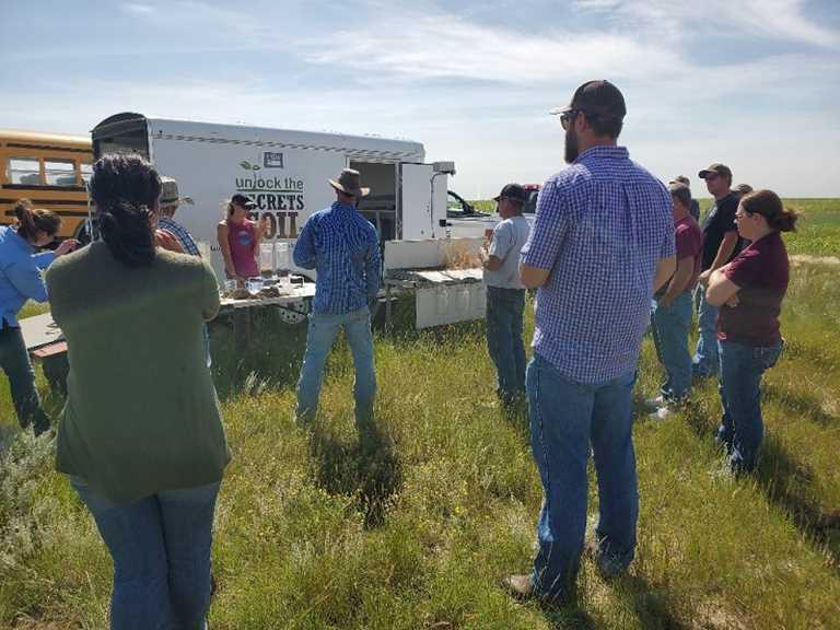 Producers observe rainfall simulator.