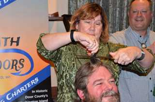 Director of Development Chris Hildebrandt allows his hair to be cut with a knife by volunteer.