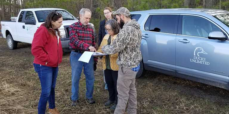 DU/NRCS biologist Chase Colmorgen, right, meets with landowners and NRCS partners on a project site in Virginia.