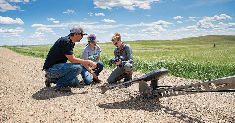 Dr. Susan Felege, associate professor at  the University of North Dakota, works with students to launch a drone to survey breeding ducks.