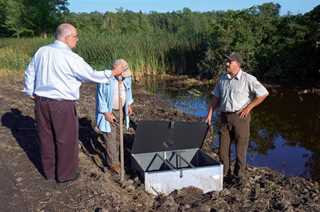 Iroquois NWR Manager Tom Roster and volunteers from the Friends of Iroquois inspect the newly installed water-control structure.